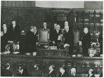 Il capo dello Stato Einaudi, con in mano i fogli del suo discorso, si intrattiene con Bonomi nei banchi della presidenza della Camera; tra i presenti si riconoscono Gronchi e, nei sottostanti banchi del governo, De Gasperi
