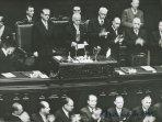 Il capo dello Stato Einaudi legge il discorso di insediamento; i deputati presenti applaudono; accanto a lui si vedono Gronchi, Bonomi, Scoccimarro; dietro di intravede Mattarella e, nei banchi del governo, De Gasperi, Pacciardi, Grassi e Togni